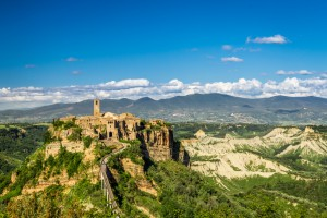 Ancient city on hill in Tuscany on a mountains background.